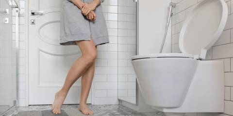 A woman standing in the bathroom with legs crossed suffering incontinence issues.