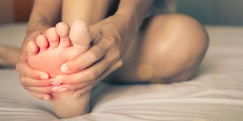 A woman massaging pain in his foot