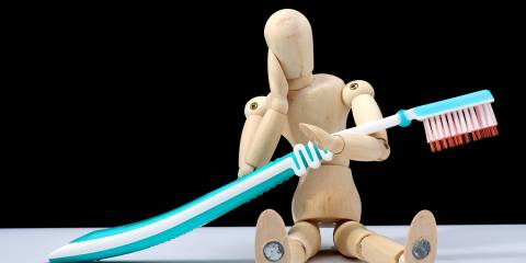 A small wooden figure with a toothache holding a full-size toothbrush