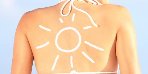 Sunscreen shaped like sun on woman's back