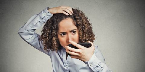 A woman with beautiful curly hair, checking her hairline for thinning hair