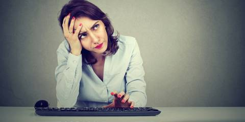 Woman trying to remember sitting at a keyboard.