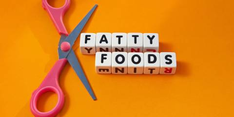 Text ' fatty foods ' inscribed in black uppercase letters on small white cubes with scissors to symbolize cut out , orange background.