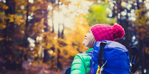 a woman hiking through the fall foliage