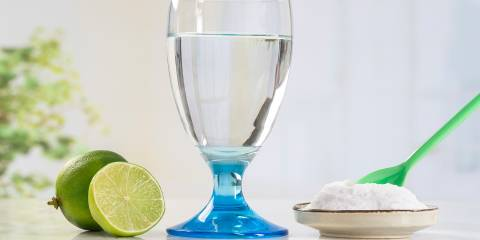 A glass of water, a sliced lime and a small dish of baking soda with a green spoon in it.