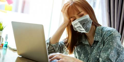 a fatigued woman in a mask working from home