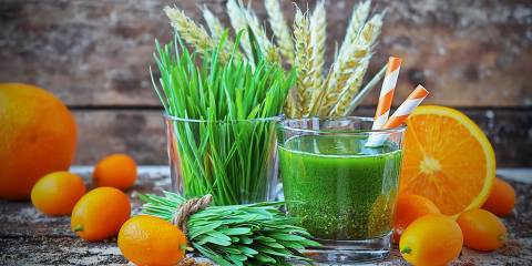 A green smoothie with wheatgrass and oranges
