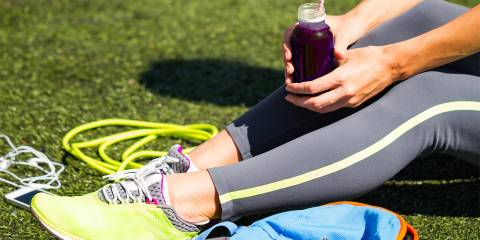 A runner taking a break to drink her beetroot juice