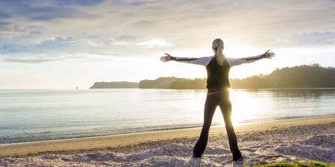 energized woman on the beach in the morning