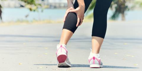 Woman holding calf during a muscle spasm while running.