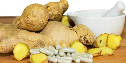 Ginger root accompanied by a motor and pestal with supplements capsules.
