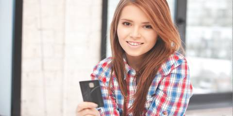 Girl holding debit card.
