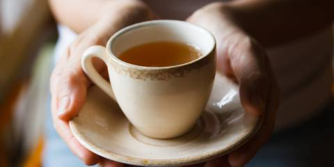 A woman holding a freshly brewed cup of tea.