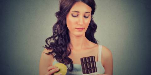 Woman with chocolate and apple trying to make a healthy choice.