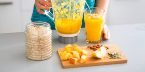 A woman making a protein smoothie with fresh fruits, nuts, and seeds
