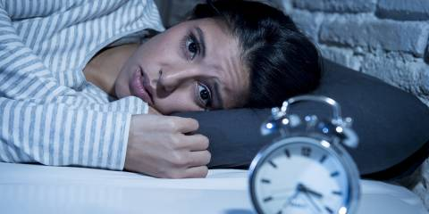 Woman awake in bed with clock in view.