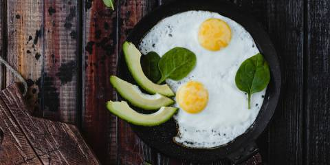Fried eggs in a cast iron pan, with avocado slices garnished with spinach.
