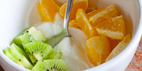 a bowl of yogurt with oranges and kiwi