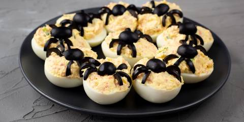 Spooky halloween deviled eggs with olive spiders