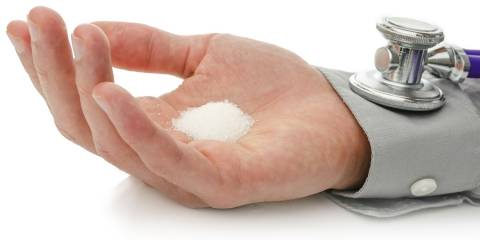 A man's hand, palm side up holding a pile of sugar in it. A stethoscope on his wrist.