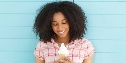 Woman smiling holding an ice cream cone.