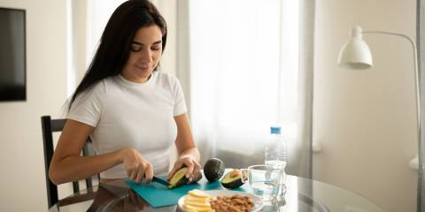 Woman following a keto diet smiling while cutting up an avocado for a snack.