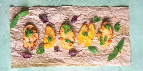 Crispy potatoes on parchment paper garnished with herbs and greens on a light blue background.