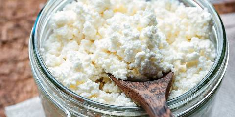 Homemade ricotta cheese is a jar with a wooden spoon.