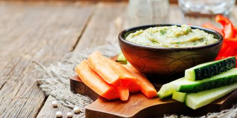 Lite Miso Dip in a wooden bowl surrounded by vegetable sticks with a rustic background.