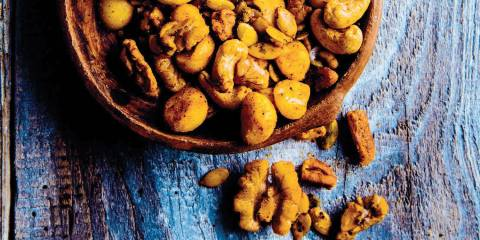 Taco-Spiced Mixed Nuts in a wooden bowl on a blue stained wooden table.