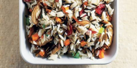 Wild Rice and Mushroom Stuffing in a white serving dish on a tan background.