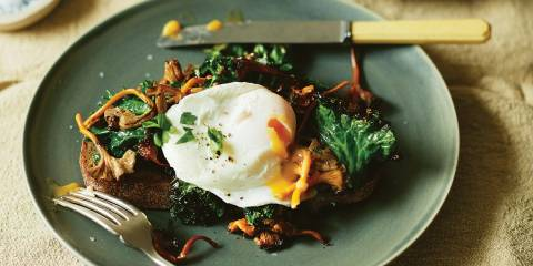 Chanterelle Toast with Poached Eggs and Kale on a plate with yolk pouring out of the egg.