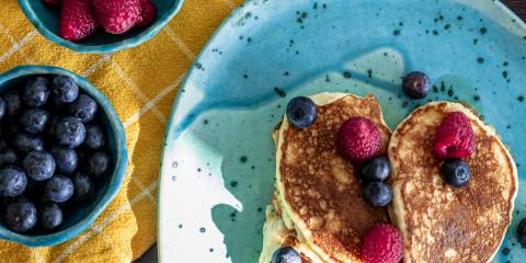 a plate of pancakes and bowls of berries