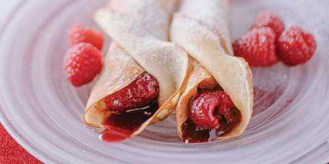 Jam Crêpes with Vanilla Sugar on a white swirled glass plate garnished with raspberries.