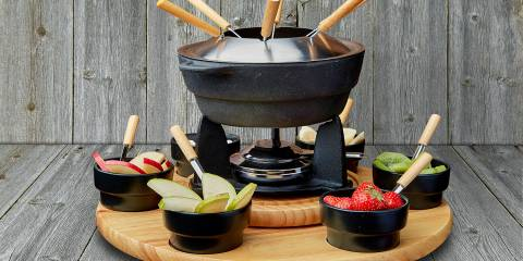 Fruit fondue on a plate on the background of wooden boards