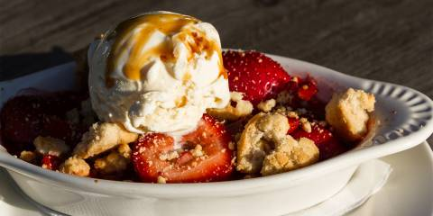 a dish of strawberry-rhubarb crisp topped with ice cream