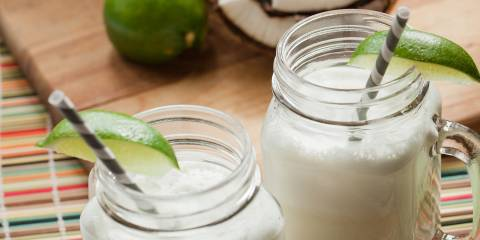 Two mug-handle mason jars full of coconut-lime cooler