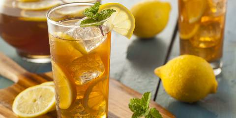 Freshly made iced tea in a glass with lemon.