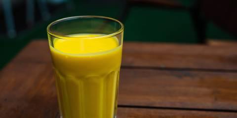 a tall glass of a creamy mango smoothie