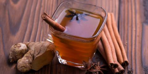 A glass of cranberry-apple cider served with a cinnamon stick