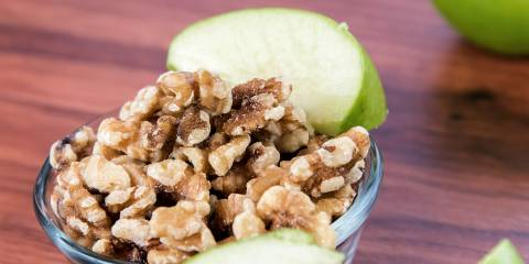 A bowl of chopped walnuts and green apple slices