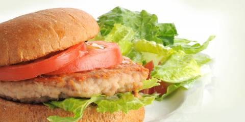 Chicken burger with sliced tomato and lettuce on toasted bun