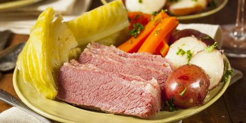 A plate of corned beef and cabbage with potatoes and carrots