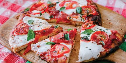 Margherita Flatbread Pizza on a wooden pizza board, cut and ready to serve.
