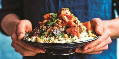 A man holding a heaping plate of Veggie Tagine