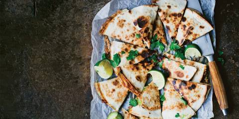 Top view of Portobello and Avocado Quesadillas on parchment paper cut into wedges to serve.