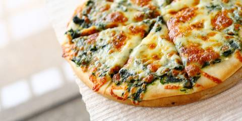 Spinach pizza with cheese on white table