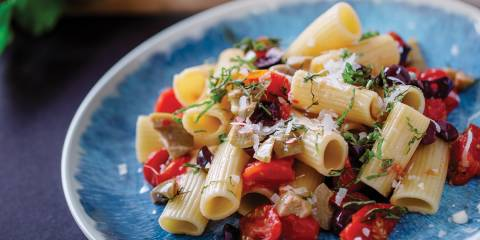 Rigatoni with Fresh Cherry Tomatoes and Olives on a blue plate ready to serve.