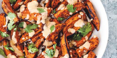 sweet potatoes plated with tahini and cilantro