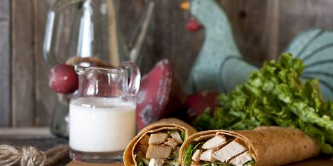 Chicken wrap with ranch dressing cut in half displayed on a cutting board. Farmhouse style background.